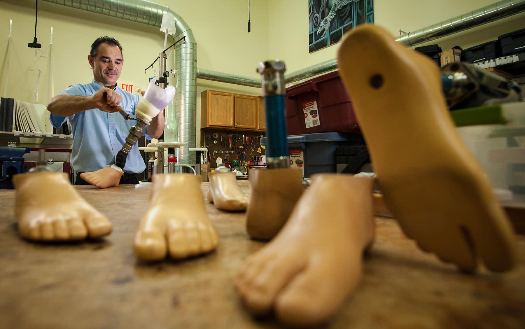 POA employee assembling prosthetics.
